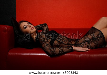 Young woman in black dress lying on red sofa - stock photo