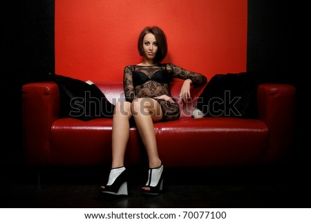 Young woman in black dress sitting on red couch - stock photo