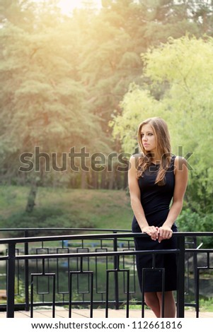 Young woman in black dress walking in park - stock photo