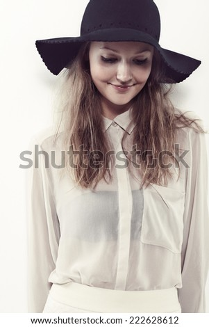 Young woman in black hat looking down in studio, smiling - stock photo