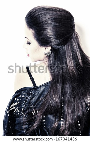 young woman in black leather jacket with rivets and spines, back shot, studio  - stock photo