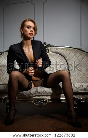 Young woman in black lingerie sitting on the couch - stock photo