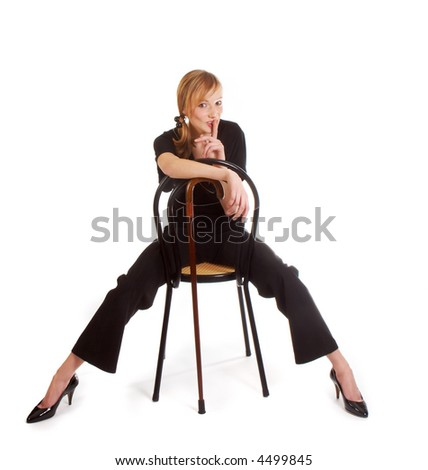 Young woman in black outfit putting her finger on her lips - stock photo
