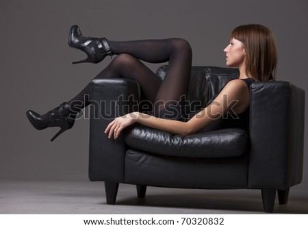 young woman in black pantyhose and heels relaxing on the chair - stock photo