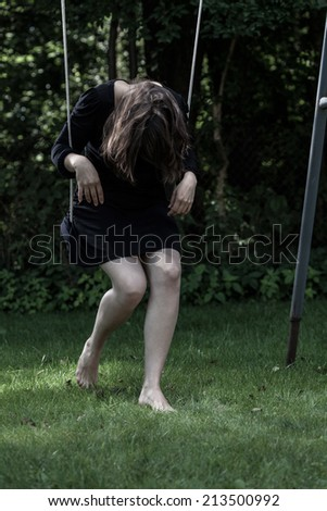 Young woman in black sitting on swing with her head down - stock photo
