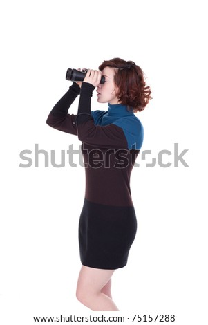 Young woman in blue and black dress , strnding profile to the camera, looking through a pair of binoculars.