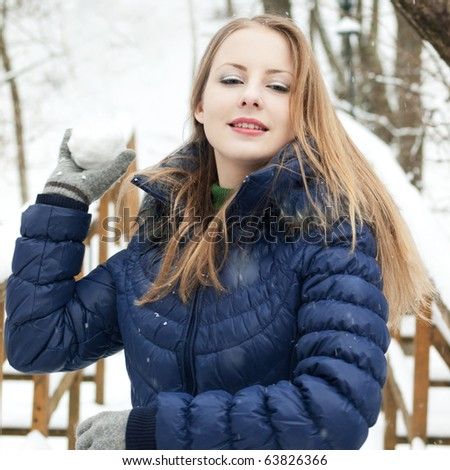 young woman in blue coat outdoors playing with snow in snow forest - stock photo