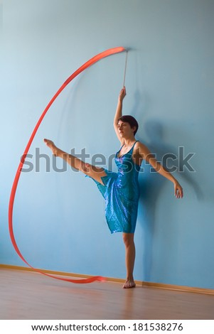 Young woman in blue dress doing gymnastic exercise