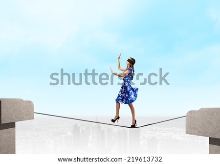 Young woman in blue dress walking on rope above gap