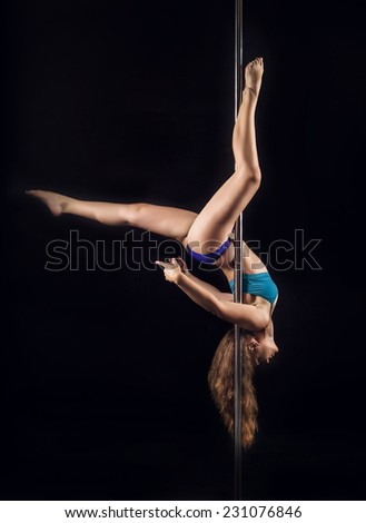 Young woman in blue set of clothes pole dancing on black background. Beautiful fit fitness sport model - stock photo