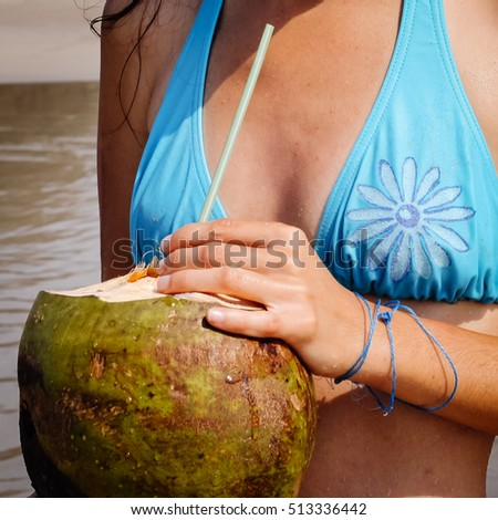 Young woman in blue swimsuit with coconut cocktail on the beach in Goa, India
