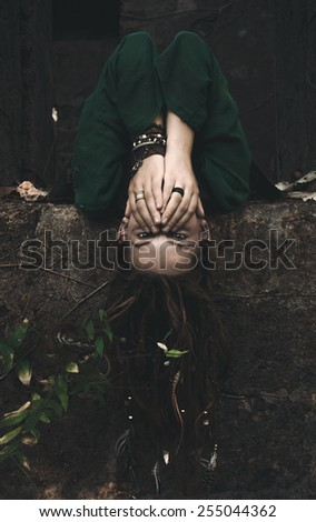 Young Woman in Boho Fashion Lying Down on an Old Concrete Platform with Head Hanging Over the Edge While Covering her Mouth. - stock photo