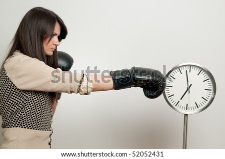 Young woman in boxing gloves beating the clock - stock photo