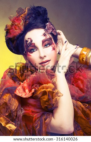 Young woman in bright orange dress and with artistic visage and hairstyle - stock photo