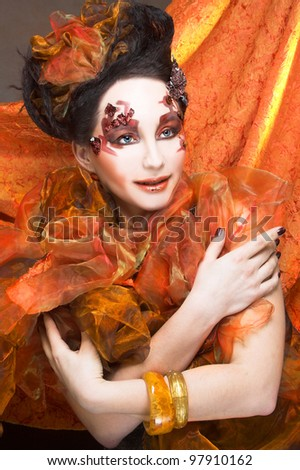Young woman in bright orange dress and with artistic visage and hierstyle