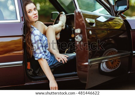Young woman in burgundy car , tinted photo