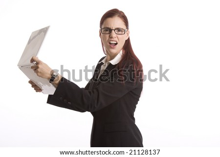 Young woman in business attire angrily holding a laptop computer - stock photo