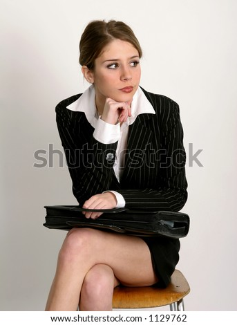 Young woman in business suit sitting on chair with briefcase in her lap - stock photo