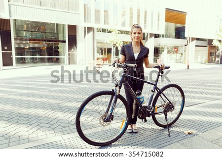 Young woman in business wear commuting on bicycle in city - stock photo