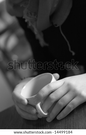 Young woman in cafe sits with empty cup of coffee