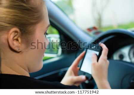 Young woman, in car with mobile phone , checking her text message or her navigation - stock photo