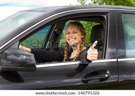 Young woman in car with thumb up - stock photo