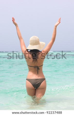 young woman in caribbean sea with open hands - stock photo