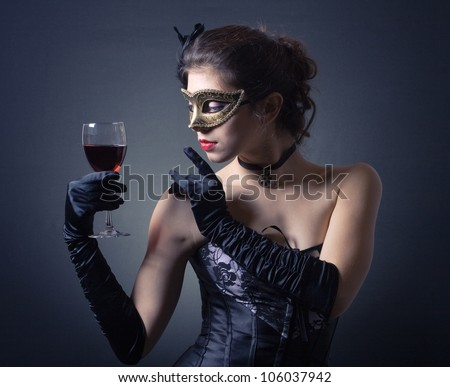 young woman in carnival mask and a glass of red wine. - stock photo