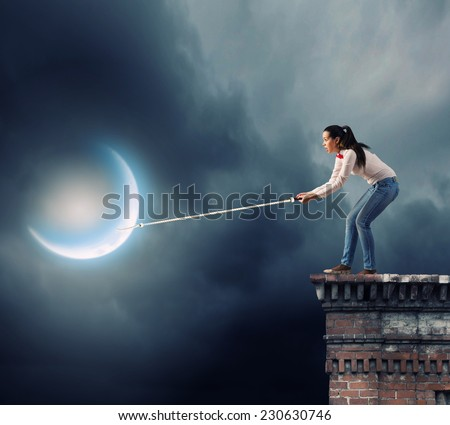 Young woman in casual catching moon with rope - stock photo