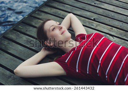 Young woman in casual clothing resting and looking on sky outdoors on wooden bridge portrait. - stock photo