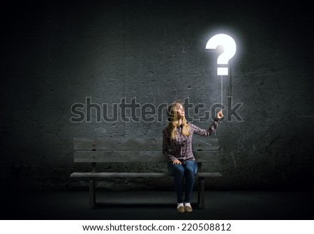 Young woman in casual holding balloon shaped like question mark - stock photo