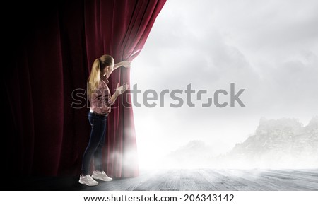 Young woman in casual opening red curtain and looking at clear sky - stock photo