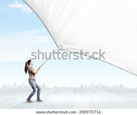 Young woman in casual pulling white blank banner - stock photo