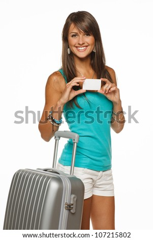 Young woman in casual standing with silver travel bag holding empty credit card, isolated on white background - stock photo