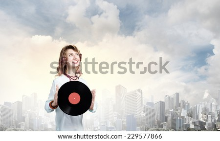 Young woman in casual wearing headphones and holding disco plate