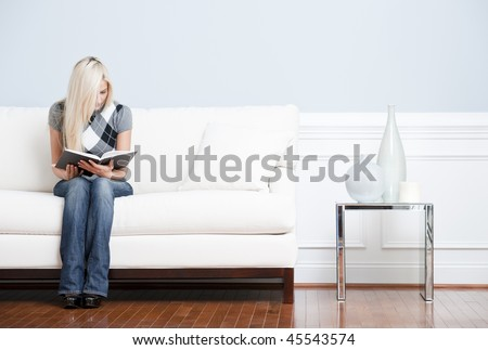 Young woman in checkered shirt and blue jeans sitting on white sofa reading a book. Horizontal shot. - stock photo