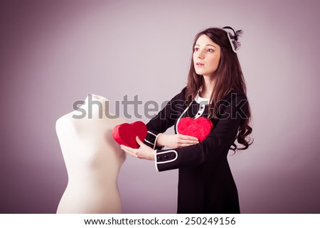 Young woman in classic black dress giving heart to mannequin on studio background - stock photo
