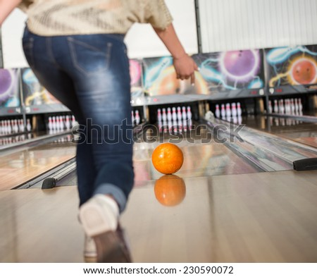 Young woman in club for bowling is throwing ball. - stock photo