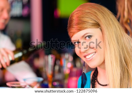Young woman in club or bar drinking champagne and is flirting with the barkeeper - stock photo