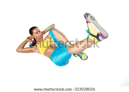 Young woman in colorfully sportswear doing exercise on white backround - stock photo