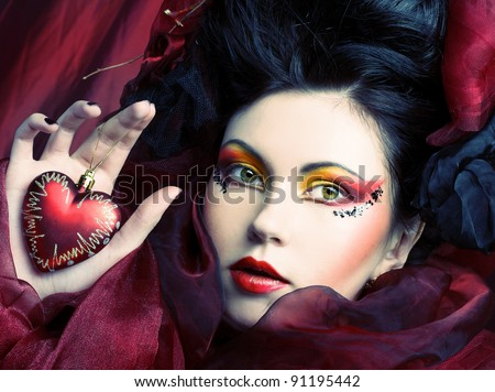 Young woman in creative image with red heart in her hands. - stock photo