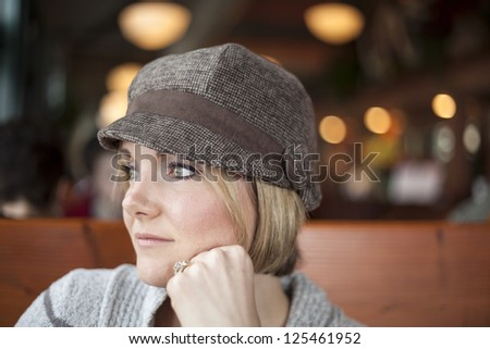 Young woman in cute brown hat staring off into the distance - stock photo