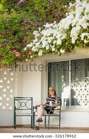 Young woman in cute straw hat and summer dress sitting on chair on terrace of white cottage house with flower roof, holding cellphone, looking at screen, using app, messaging - stock photo