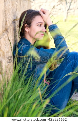 young woman in depression near the stone wall - stock photo