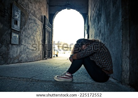 Young woman in depression sitting in the floor at the gateway arch . - stock photo