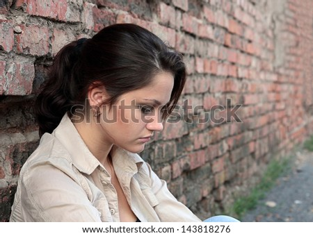Young woman in despair sitting against a brick wall - stock photo