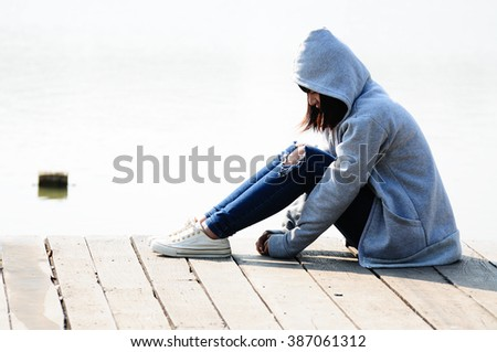 Young Woman in Despair Sitting Near River - stock photo