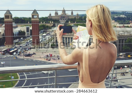 Young woman in dress photographing urban view with mobile phone camera during summer journey, female tourist taking picture of active life in the city with her smart phone while standing on viewpoint - stock photo