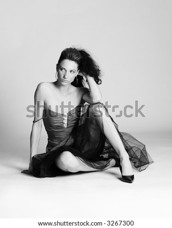 Young woman in dress sitting on floor