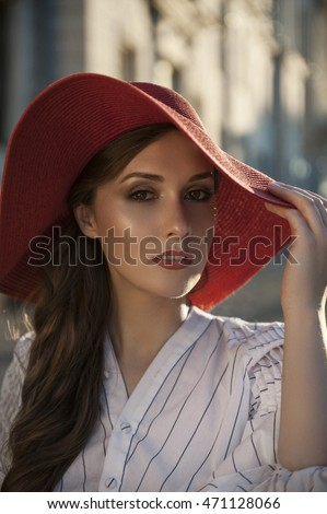 Young woman in elegant dress and in red hat. Stylish woman